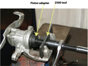 Lisle 25000 Rear Disc Brake Caliper Tool in use off the vehicle. Showing how the tool pushes against the piston and rotates it at the same time