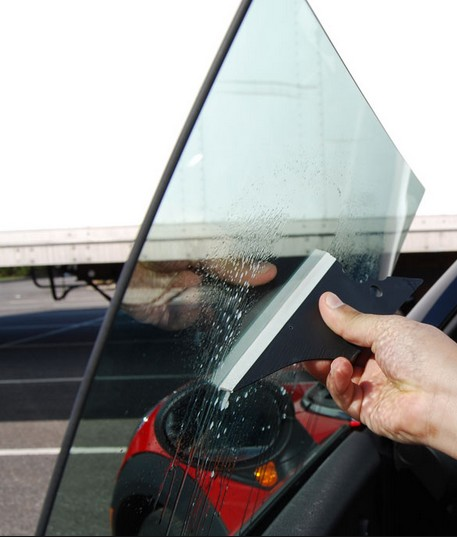 Use a squeegee to apply car window tint film