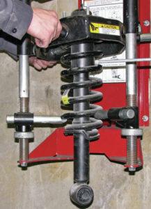 Strut in spring compressor tool to desengage strut